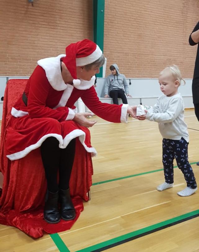 Julekonen hjælper julemanden med at dele slikposer ud